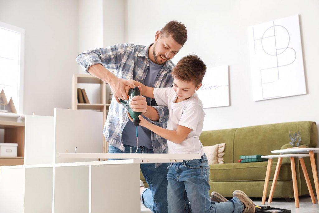 Vater und Sohn bauen zuhause Möbel zusammen