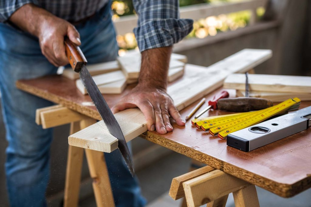 Mann sägt Holz